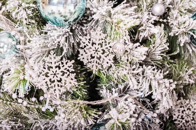 Traditionele kerst of nieuwjaar versierde boom met een zilveren sneeuwvlok speelgoed.