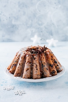 Traditionele kerstfruitcake, pudding op keramische witte standaard. bovenaanzicht.