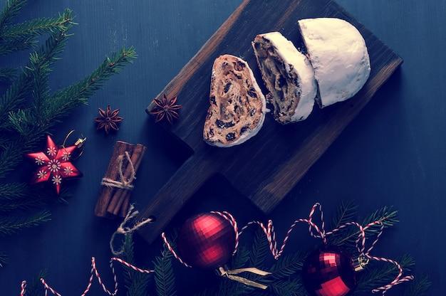 Traditionele kerstmiscake met rozijnen en noten met boomtakken en speelgoed