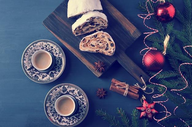 Traditionele kersttaarttaart met rozijnen en noten met boomtakken en speelgoed, en twee kopjes koffie