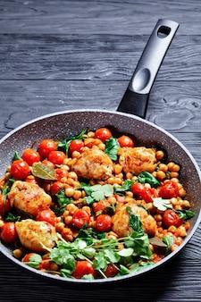 Traditionele kip en kikkererwten curry van kippendijen zonder been met cherrytomaatjes, spinazie, gember, geserveerd met verse koriander op een koekenpan op een zwarte houten tafel, bovenaanzicht, close-up