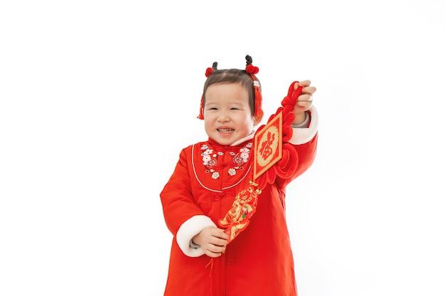 Traditionele kleding van chinees babymeisje met traditionele hanger in haar hand