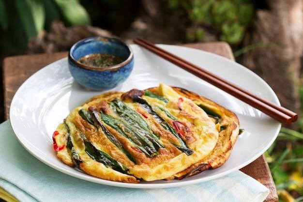 Traditionele koreaanse beignets met groene uien en chili, geserveerd met sojasaus.