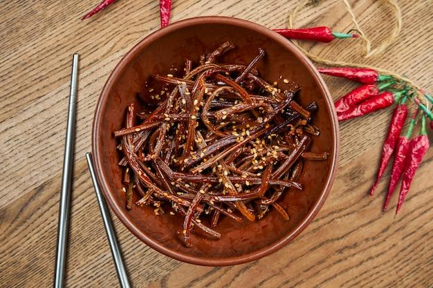 Traditionele koreaanse keuken, gebraden varen in keramische kom. bovenaanzicht