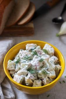 Traditionele koude aardappelsalade met uien en kruiden op een linnen tafellaken achtergrond. rustieke stijl.