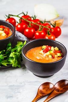 Traditionele koude gazpacho tomatensoep in zwarte kom op grijs