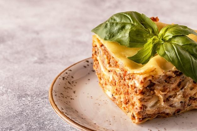 Traditionele lasagne gemaakt met rundergehakt bolognesesaus en bechamelsaus gegarneerd met basilicumblaadjes.