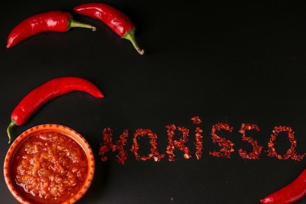 Traditionele maghrebi hete chilipepersaus harissa op donkere achtergrond, tunesië en arabische keuken, horizontale oriëntatie, woord harissa inscriptie van droge peper