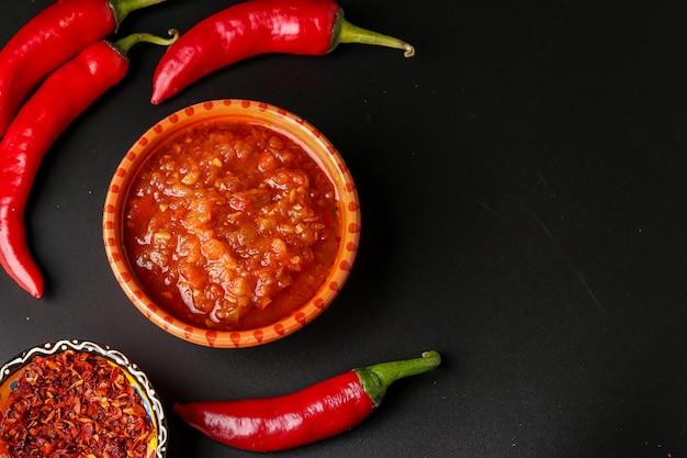 Traditionele maghrebi hot chili peper saus plakken harissa op donkere ondergrond, tunesië en arabische keuken, horizontale oriëntatie, kopie ruimte