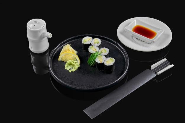 Traditionele maki sushi rolt met avocado op een zwarte plaat in samenstelling met sojasaus en eetstokjes op een zwarte ondergrond. japans eten. foto voor het menu
