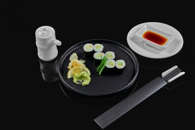 Traditionele maki sushi rolt met komkommer op een zwarte plaat in samenstelling met sojasaus en eetstokjes op een zwarte ondergrond. japans eten. foto voor het menu