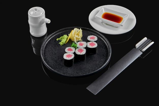 Traditionele maki sushi rolt met tonijn op een zwarte plaat in samenstelling met sojasaus en eetstokjes op een zwarte ondergrond. japans eten. foto voor het menu