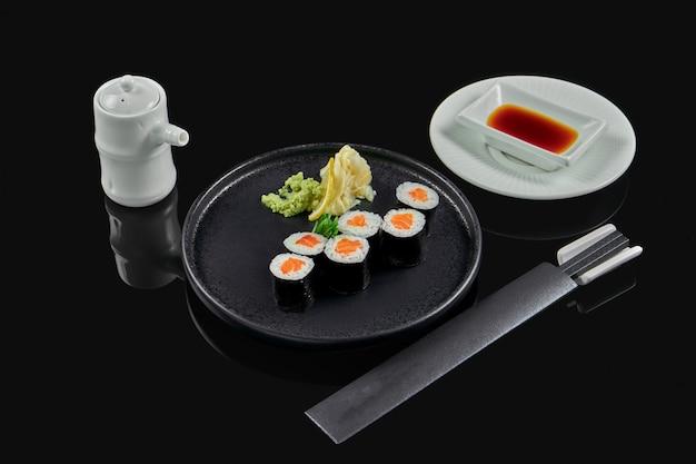 Traditionele maki sushi rolt met zalm op een zwarte plaat in samenstelling met sojasaus en eetstokjes op een zwarte ondergrond. japans eten. foto voor het menu