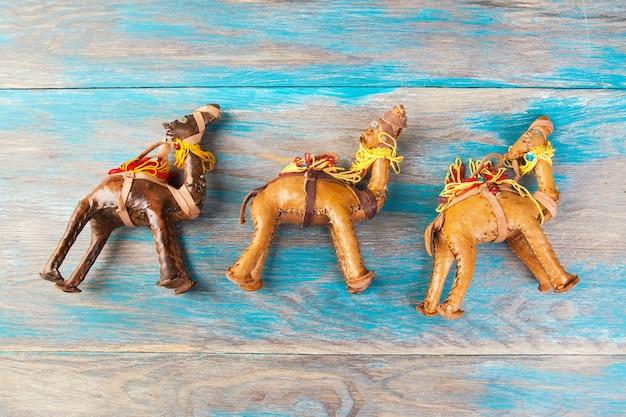 Traditionele marokkaanse souvenirs, drie lederen kamelen op blauwe houten achtergrond.