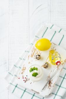 Traditionele mayonaisesaus in witte ceramische kom en ingrediënten voor de voorbereiding op wit houten.