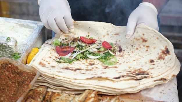 Traditionele mediterrane keuken. de mens maakt ekmek met vis, groenten, tomaten en smaakmakers op straatmarkt, handen in handschoenen close-up. cook wikkelt de vulling in pitabroodje.