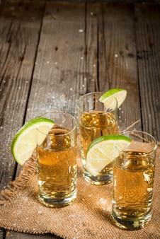 Traditionele mexicaanse alcoholische drank is een gouden tequila in lange glazen met een schijfje limoen en zout op de achtergrond op een rustieke houten tafel