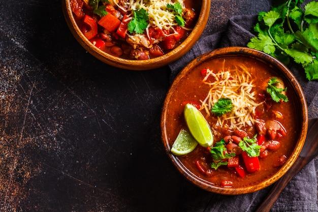 Traditionele mexicaanse bonensoep met vlees en kaas in houten kom