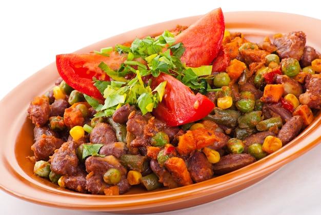Traditionele mexicaanse chili met bruine bonen en tomaat op witte achtergrond