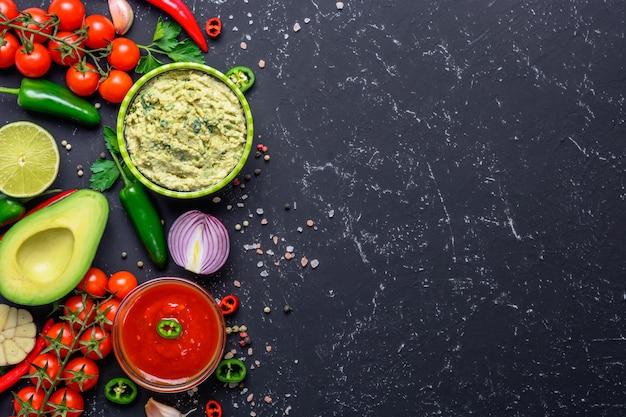 Traditionele mexicaanse latijns-amerikaanse salsasaus en guacamole en ingrediënten op zwarte stenen tafel. bovenaanzicht achtergrond met copyspace