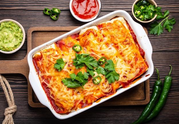 Traditionele mexicaanse schotel enchiladas met vlees, rode chilisaus en kaas in witte braadpan schotel op rustieke houten achtergrond, geserveerd met guacamole en tomaat dips. close-up, bovenaanzicht