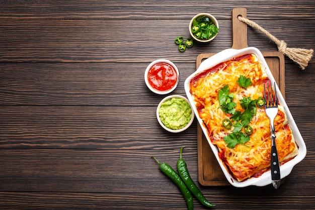 Traditionele mexicaanse schotel enchiladas met vlees, rode chilisaus, kaas in witte braadpan schotel op rustieke houten achtergrond, geserveerd met guacamole en tomaat dips. close-up, bovenaanzicht, ruimte voor tekst