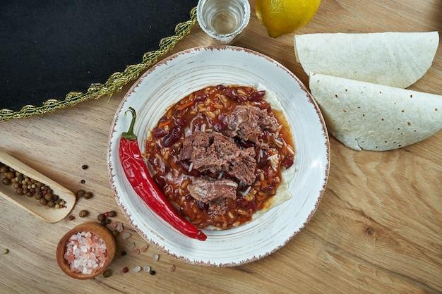 Traditionele mexicaanse taco's met bonen, chili peppers, rundvlees in witte keramische plaat op houten tafel. lekkere chili con carne beef burrito's in maïstaco's