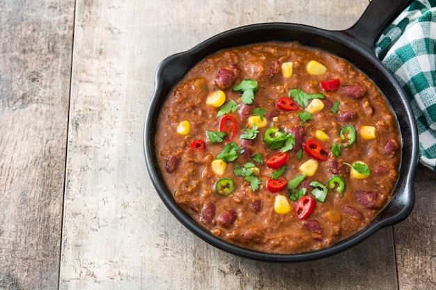 Traditionele mexicaanse tex mex chili con carne in een koekenpan op houten tafel kopie ruimte
