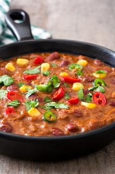 Traditionele mexicaanse tex mex chili con carne in een koekenpan op houten tafel