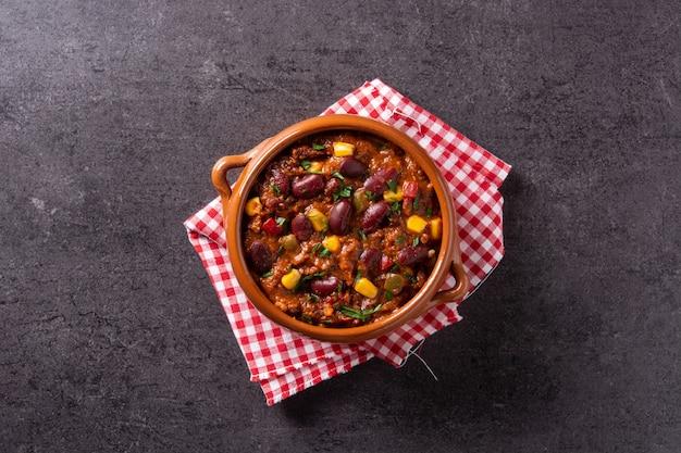 Traditionele mexicaanse tex mex chili con carne in een kom op zwarte achtergrond.