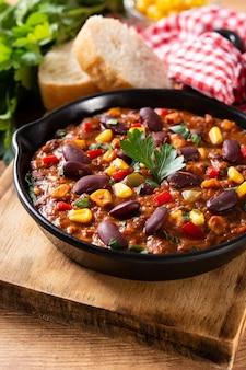 Traditionele mexicaanse tex mex chili con carne in ijzeren pan op houten tafel