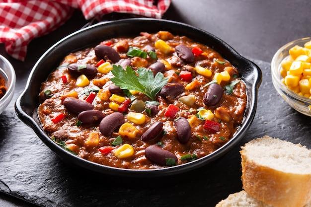 Traditionele mexicaanse tex mex chili con carne in ijzeren pan op zwarte achtergrond