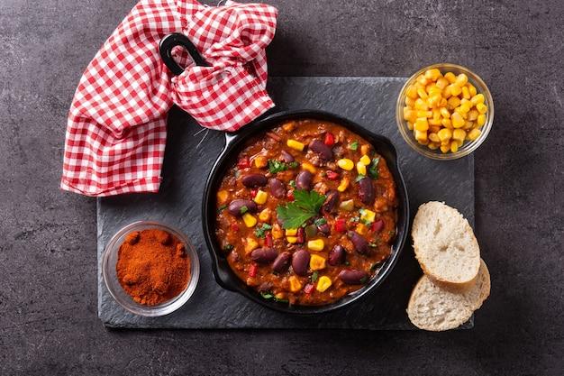 Traditionele mexicaanse tex mex chili con carne in ijzeren pan op zwarte stenen achtergrond