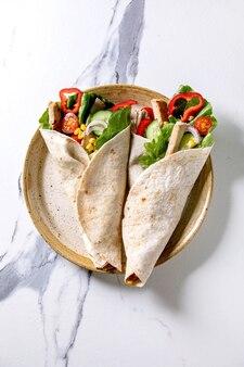 Traditionele mexicaanse tortila wrap met varkensvlees en groenten in keramische plaat over wit marmeren oppervlak. bovenaanzicht, plat gelegd. zelfgemaakt fastfood