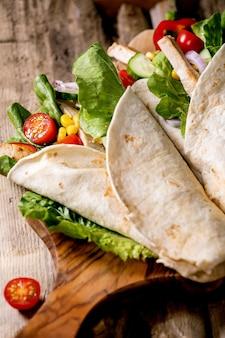 Traditionele mexicaanse tortila wrap met varkensvlees en groenten op houten snijplank over bruin houten oppervlak. bovenaanzicht, plat gelegd. detailopname. zelfgemaakt fastfood