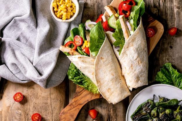 Traditionele mexicaanse tortila wrap met varkensvlees en groenten op houten snijplank versierd met witte textiel servet maïs en gegrilde jalapenos over bruin houten oppervlak. bovenaanzicht, plat gelegd