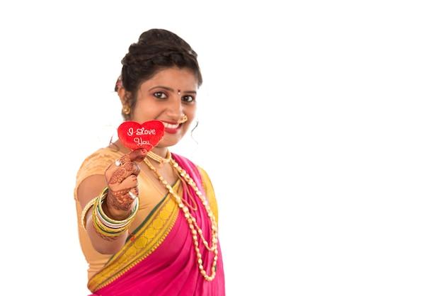 Traditionele mooie indiase jonge meisje in saree poseren met hart op wit