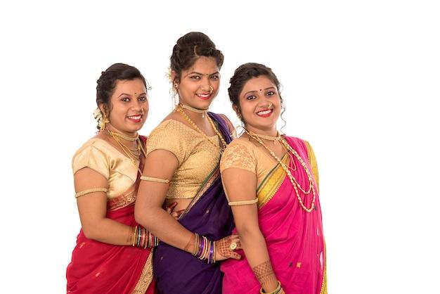 Traditionele mooie indiase jonge meisjes in saree poseren op wit