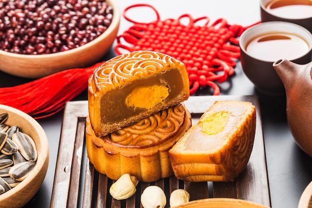 Traditionele mooncakes op lijst die met theekopje plaatst.
