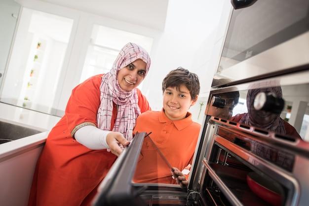 Traditionele moslimvrouw die fornuis gebruikt