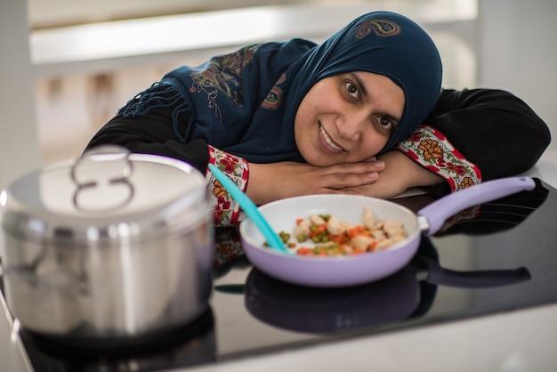 Traditionele moslimvrouw die in de keuken werkt