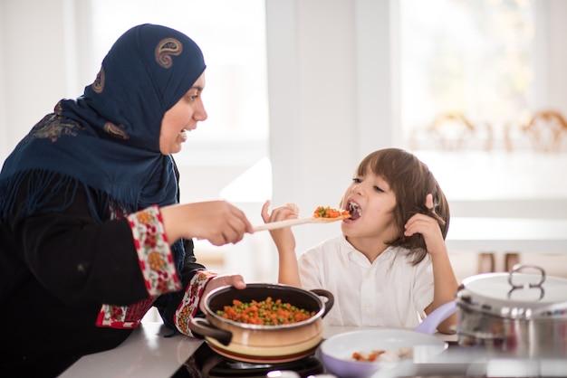 Traditionele moslimvrouw met leuk kind in huis