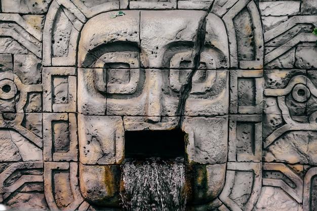 Traditionele nationale indiase totem. totempaal beeldhouwkunst. oude houten masker. maya en azteken symbolische religieuze goden gezichten. etnische heidense aanbidding en afgoderij.