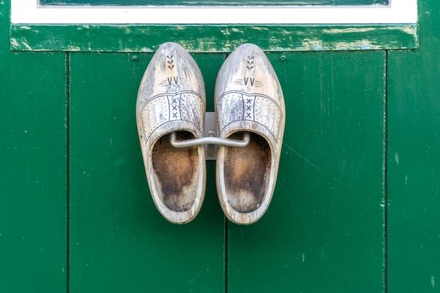 Traditionele nederlandse houten schoenen die bij een muur hangen