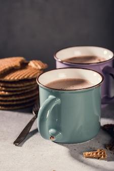 Traditionele nederlandse koekjesstroopwafels over oude mok met chocolademelk op grijze oppervlakte met exemplaarruimte. retro stijl afgezwakt