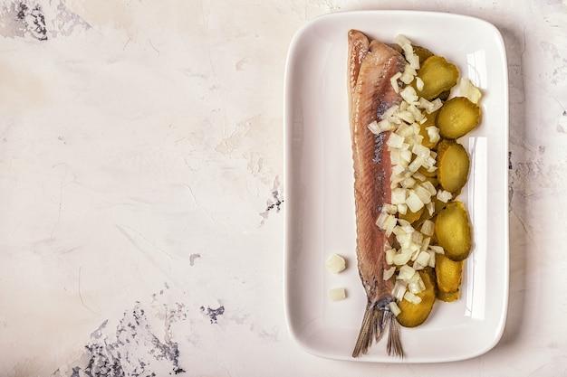 Traditionele nederlandse rauwe haring met uien en augurken op wit.