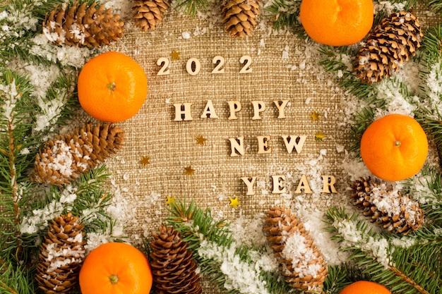 Traditionele nieuwjaars- en kerstachtergrond met de beste wensen, met letters en cijfers van het komende jaar. mandarijnen, vuren takken, kegels.