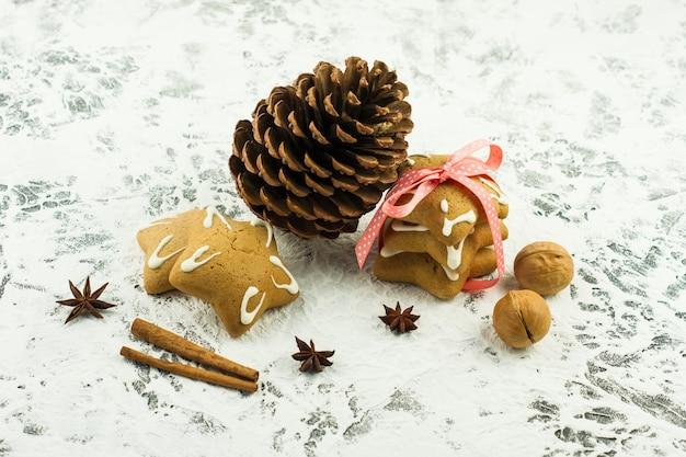 Traditionele nieuwjaarsachtergrond met kegels, noten, kaneelstokjes en stervormen gemberkoekjes op witte achtergrond.