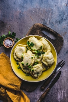 Traditionele oekraïense gestroomde aardappelvareniki of dumplings geserveerd in een kom en groene kruiden