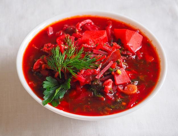 Traditionele oekraïense russische borsjt met bonen op de kom. plaat van rode biet wortel soep borsch.
